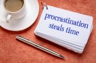 procrastination steals time reminder on a stack of  index cards with a cup of coffee